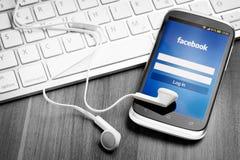 Uso de Facebook en la pantalla elegante del teléfono. Imagen de archivo libre de regalías