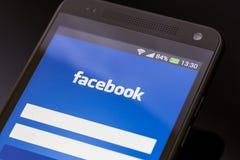 Uso de Facebook en la pantalla elegante del teléfono. imagen de archivo
