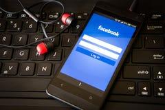 Uso de Facebook en la pantalla elegante del teléfono imagen de archivo