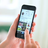 Uso de Instagram en el iPhone 5S de Apple Foto de archivo
