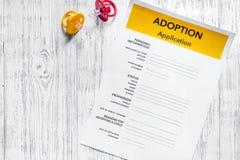 Uso de la adopción cerca del pacificador del bebé en copyspace de madera ligero de la opinión superior del fondo de la tabla Imagen de archivo