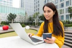 Uso de la mujer del ordenador portátil así como el teléfono móvil Imágenes de archivo libres de regalías