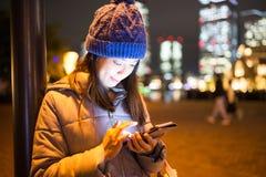 Uso de la mujer del teléfono móvil en ciudad en la noche Foto de archivo