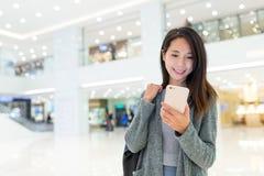 Uso de la mujer del teléfono móvil en plaza de compras Fotografía de archivo libre de regalías