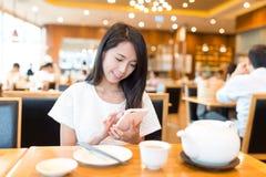 Uso de la mujer del teléfono móvil en restaurante Fotos de archivo libres de regalías