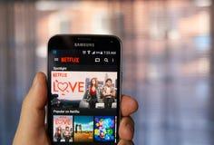 Uso de Netflix en el teléfono celular foto de archivo
