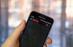 Uso de Netflix en el teléfono celular fotografía de archivo libre de regalías