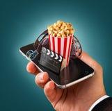 Uso de Smartphone para los boletos en línea del cine de la compra y de la reservación Películas y vídeo de observación Live imagen de archivo libre de regalías