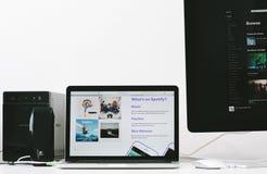 Uso de Spotify en la pantalla del ordenador portátil de Apple Imagen de archivo