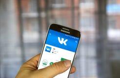 Uso de Vkontakte en la pantalla de Samsung S7 Imágenes de archivo libres de regalías