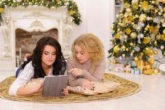 Uso del artilugio moderno del regalo por dos hermanas que mienten en piso en brigh Imagen de archivo