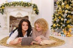 Uso del artilugio moderno del regalo por dos hermanas que mienten en piso en brigh Imagen de archivo libre de regalías