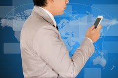 Uso del hombre de negocios un teléfono elegante para el negocio Imagen de archivo