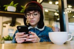 Uso del inconformista de la chica joven el teléfono y consumición de una bebida caliente en un café agradable Imagen de archivo libre de regalías