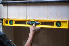 Uso del lavoratore dell'industria che costruisce a livello per controllare il bordo dell'equilibrio della parete a controllare li Fotografie Stock