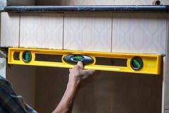 Uso del lavoratore dell'industria che costruisce a livello per controllare il bordo dell'equilibrio della parete a controllare li Fotografia Stock Libera da Diritti