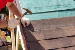 Uso del trabajador del constructor del Roofer que un martillo para instalar la techumbre escalona Foto de archivo libre de regalías