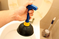 Uso del tuffatore per una ciotola di toilette fotografia stock