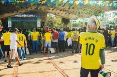 Uso dell'uomo anziano verde e giallo guardando una partita del mondo c immagini stock