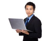 Uso dell'uomo d'affari del computer portatile Immagine Stock