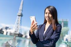 Uso della donna di affari del cellulare a Nagoya immagine stock