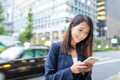 Uso della donna di affari del cellulare in via di Tokyo Fotografia Stock