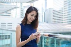 Uso della giovane donna del telefono cellulare Fotografia Stock