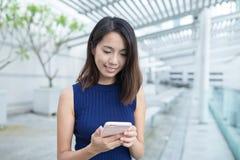 Uso della giovane donna del telefono cellulare Immagini Stock Libere da Diritti