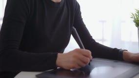 Uso della giovane donna una tavola e uno stilo del grafico lavorare dietro uno schermo di computer moderno video d archivio