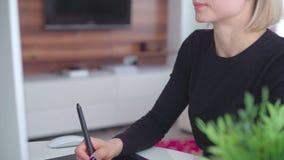 Uso della giovane donna una tavola e uno stilo del grafico lavorare dietro uno schermo di computer moderno stock footage