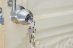 Uso destravado da mão do botão a chave para destravar a madeira da porta do botão de porta fotos de stock