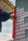 Uso do trabalhador da construção um nível de espírito verificar telhas decorativas na fachada da construção fotografia de stock royalty free