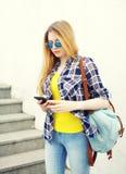 Uso grazioso della ragazza occhiali da sole e zaino facendo uso dello smartphone immagini stock libere da diritti