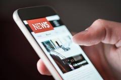 Uso móvil de las noticias en smartphone Noticias en línea de lectura del hombre en página web con el teléfono móvil imagen de archivo libre de regalías