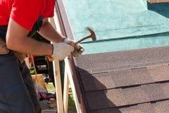 Uso que do trabalhador do construtor do Roofer um martelo para instalar o telhado shingles Fotos de Stock Royalty Free