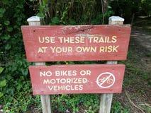 Uso rojo que estos rastros bajo su propio riesgo firman y ningunas bicis o vehículos motorizados permitidos firman cerca de rastr fotografía de archivo