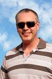 uso sorridente degli occhiali da sole dell'uomo Fotografie Stock