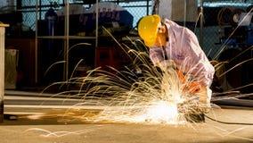 Usos do trabalhador que moem o metal cortado, foco na linha clara instantânea de sha Foto de Stock Royalty Free