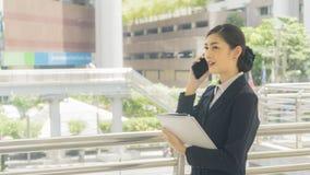Usos e negociações asiáticos da mulher de negócio no telefone celular com papel w Foto de Stock Royalty Free