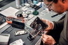 Usos lente de aumento e pinça do recruta reparar o smartphone danificado na oficina fotografia de stock royalty free