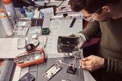Usos lente de aumento e pinça do recruta reparar o smartphone danificado na oficina foto de stock royalty free