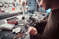 Usos lente de aumento e pinça do recruta reparar o smartphone danificado na oficina imagem de stock royalty free