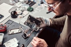 Usos lente de aumento e pinça do recruta reparar o smartphone danificado na oficina imagens de stock royalty free