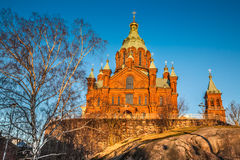 Uspenski Cathedral at sunset in Helsinki, Finland. Beautiful view of famous Eastern Orthodox Uspenski Cathedral (Uspenskin katedraali) on a hill in the golden stock images