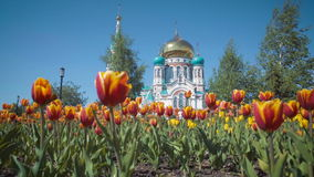 Uspensky Cathedral in Omsk on background of beautiful tulips. Uspensky Cathedral in Omsk on the background of beautiful tulips stock video footage