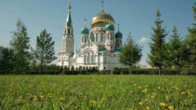 Uspensky Cathedral in Omsk on background of green lawn with yellow dandelions. Uspensky Cathedral in Omsk on the background of green lawn with yellow dandelions stock video footage
