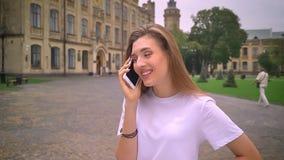 Uspokaja rozmowę telefoniczną śliczna caucasian dziewczyna i zaświeca, stoi prosto na antycznej pięknej ulicie, dzień