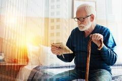 Uspokaja starzejącego się osoby obsiadanie i patrzeć fotografię w jego ręki fotografia royalty free