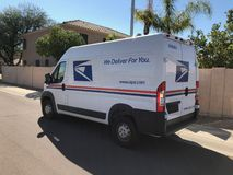 USPS Delivery Van In Arizona. A United States Postal Service, USPS, collection and delivery van in a residential neighborhood. The USPS is responsible for Stock Photography