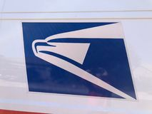 USPS Logo. A United States Postal Service, USPS, collection and delivery van in a residential neighborhood. The USPS is responsible for providing postal service stock photo